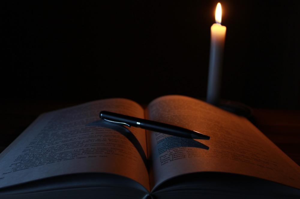 Book open in a dark room with a lit candle nearby and a pen lying across the pages